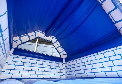 Large covered blue white bouncy castle in castle theme for sale for children. Order bounce houses online at JB Inflatables UK
